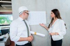 Geschäftsmann und Frau, die Architektenplan darstellen Herstellung von PR stockbilder
