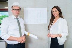 Geschäftsmann und Frau, die Architektenplan darstellen Herstellung von PR lizenzfreie stockbilder