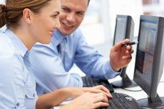 Geschäftsmann und Frau, die an Computern arbeiten Stockbilder
