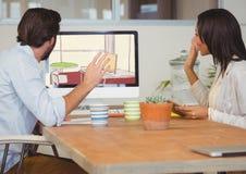 Geschäftsmann und Frau, die an dem Büro mit dem Computer auf dem Design des neuen Büros arbeiten Stockbild