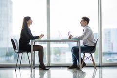 Geschäftsmann und Frau, die eine Diskussion im Büro vertraulich bei Tisch gegen Fenster hat lizenzfreies stockfoto