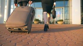 Geschäftsmann und Frau, die zum Flughafen mit ihrem Gepäck gehen Tragender Koffer des jungen Geschäftsmannes auf Rädern und stock video footage