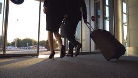 Geschäftsmann und Frau mit dem Gepäck, das vom Flughafen zur Stadtstraße geht Folgen Sie zu tragendem Koffer des jungen Geschäfts stock video footage