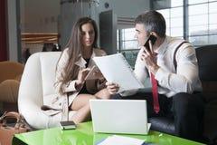 Geschäftsmann und Geschäftsfrau bei der Sitzung mit Laptop und Tablette Lizenzfreies Stockfoto