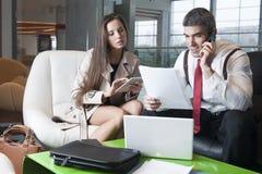 Geschäftsmann und Geschäftsfrau bei der Sitzung mit Laptop und Tablette Stockfotografie