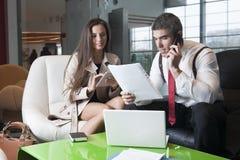 Geschäftsmann und Geschäftsfrau bei der Sitzung mit Laptop und Tablette Stockbilder
