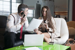 Geschäftsmann und Geschäftsfrau bei der Sitzung mit Laptop und Tablette Lizenzfreie Stockfotos