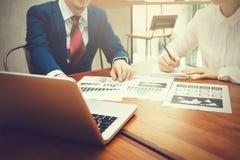 Geschäftsmann und Geschäftsfrau, die auf die Finanz- und Strategiedokumente mit Laptop während des Geschäftstreffens sich bespric Stockfotos
