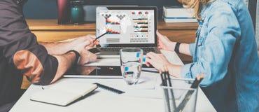 Geschäftsmann und Geschäftsfrau, die bei Tisch vor Laptop und dem Arbeiten sitzen Diagramme, Diagramme und Diagramme auf PC-Schir Lizenzfreie Stockfotos