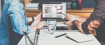 Geschäftsmann und Geschäftsfrau, die bei Tisch vor Laptop und dem Arbeiten sitzen Diagramme, Diagramme und Diagramme auf PC-Schir Stockfotografie