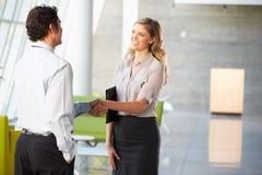 Geschäftsmann und Geschäftsfrau, die Hände im Büro rütteln Stockfoto
