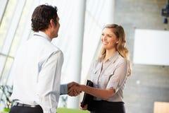 Geschäftsmann und Geschäftsfrau, die Hände im Büro rütteln Stockfotografie