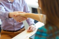 Geschäftsmann und Geschäftsfrau, die Hände im Büro rütteln Stockfotos