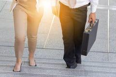 Geschäftsmann- und Geschäftsfrau, die herauf Treppe mit Taschen geht lizenzfreie stockfotos