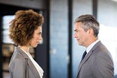 Geschäftsmann und Geschäftsfrau, die vertraulich steht Lizenzfreies Stockbild