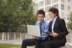 Geschäftsmann und Geschäftsfrau, die zusammen draußen an dem Laptop arbeiten Stockfotos