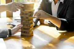 Geschäftsmann und Geschäftsfrau gruppieren Plan und Spiel jenga hölzernes b Stockbilder