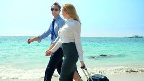 Geschäftsmann und Geschäftsfrau mit einem Koffer gehend entlang den weißen Sandstrand auf der Insel lizenzfreie stockfotos