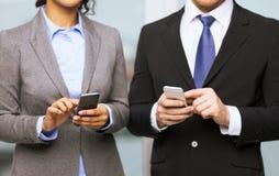 Geschäftsmann und Geschäftsfrau mit Smartphones stockbilder
