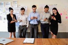 Geschäftsmann und Geschäftsfrau sich entspannen, Textnachricht auf Smartphoneschwätzchen mit Freund zu stehen und zu schreiben stockfotografie