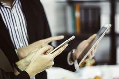 Gesch?ftsmann und Gesch?ftsfraugebrauchssmartphones und -tabletten, die an Hand mit dem Konzept der Bequemlichkeit im Einkaufen o stockfotos