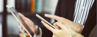 Geschäftsmann- und Geschäftsfraugebrauchssmartphones und -tabletten, die an Hand mit dem Konzept der Bequemlichkeit im Einkaufen  lizenzfreie stockbilder