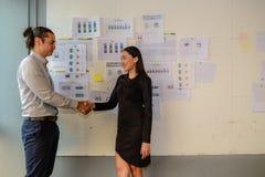 Geschäftsmann- und Geschäftsfraustand und rütteln Hände für Erfolgsgeschäftsvereinbarung stockfotografie