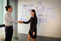 Geschäftsmann- und Geschäftsfraustand und rütteln Hände für Erfolgsgeschäftsvereinbarung lizenzfreie stockfotografie