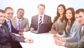 Geschäftsmann und Geschäftsteam, das am Schreibtisch sitzt Lizenzfreie Stockfotos