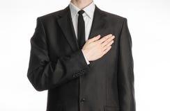 Geschäftsmann und Gestenthema: ein Mann in einem schwarzen Anzug mit einer Bindung setzte seine Hand auf seinen Kasten ein, der a Stockbild