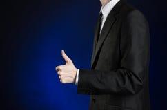 Geschäftsmann und Gestenthema: ein Mann in einem schwarzen Anzug und in einem weißen Hemd, Handzeichen Daumen-oben auf einem dunk Lizenzfreie Stockfotos