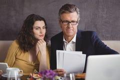 Geschäftsmann und Kollege, die über Laptop arbeiten stockfotografie