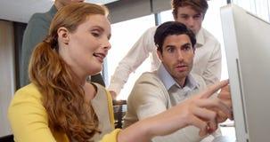 Geschäftsmann und Mitarbeiter, die über Computer am Schreibtisch sich besprechen stock video