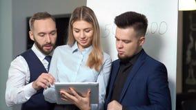 Geschäftsmann und weiblicher Diskussionsarbeitender schauender Schirm der Tablette, die informelle Teambesprechung hat stock video footage