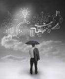 Geschäftsmann unter einem Regenschirm, der Zeichnungen betrachtet lizenzfreie stockfotos