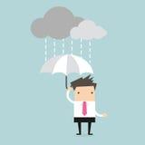 Geschäftsmann unter einem Regenschirm im Regen Stockbild