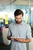 Geschäftsmann unter Verwendung der digitalen Tablette gegen Strategie auf Glas Stockfoto