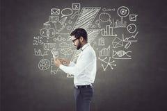 Geschäftsmann unter Verwendung der digitalen Tablette vor Tafel mit Ikonen Stockbild