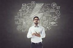 Geschäftsmann unter Verwendung der digitalen Tablette vor Tafel mit Ikonen Stockbilder