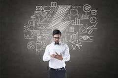 Geschäftsmann unter Verwendung der digitalen Tablette vor Tafel mit Ikonen Lizenzfreie Stockfotografie