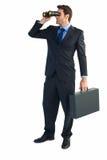 Geschäftsmann unter Verwendung der Ferngläser beim Halten eines Aktenkoffers Stockfotografie