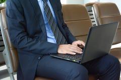Geschäftsmann unter Verwendung der Laptop-Computers beim Sitzen auf dem Stuhl am Flughafen Lizenzfreie Stockfotos