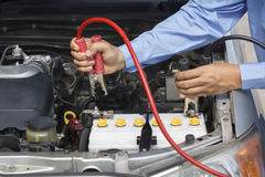 Geschäftsmann unter Verwendung der Starthilfekabel, zum eines Autos anzustellen Lizenzfreies Stockfoto