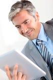Geschäftsmann unter Verwendung der Tablette stockbild