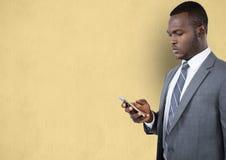 Geschäftsmann unter Verwendung des Handys über beige Hintergrund Stockfoto
