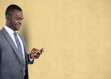 Geschäftsmann unter Verwendung des Handys über beige Hintergrund Lizenzfreie Stockfotos