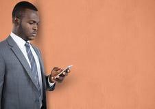 Geschäftsmann unter Verwendung des Handys über Pfirsichhintergrund Lizenzfreie Stockbilder