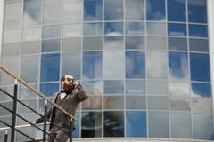 Geschäftsmann unter Verwendung des Handys außerhalb des Büros in der städtischen Stadt mit Wolkenkratzergebäuden im Hintergrund j Lizenzfreie Stockfotografie