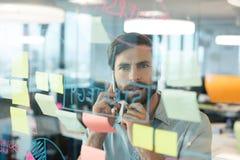 Geschäftsmann unter Verwendung des Handys beim Betrachten von den Plänen geschrieben auf Glas Lizenzfreie Stockfotografie