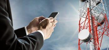 Geschäftsmann unter Verwendung des Handys, mit Satellitenschüsseltelekommunikationsnetz auf Telekommunikationsturm auf blauem Him Stockbilder